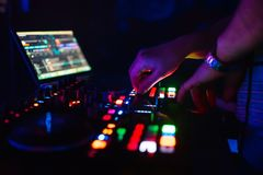 Hands of a professional DJ playing and mixing music for a slumber party royalty free stock photo