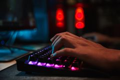 Hands of professional gamer boy playing video games on computer. In dark room using backlit colorful keyboard royalty free stock photography