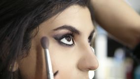 Hands of professional make-up artist applying eyeshadow to the model`s eye using special brush. Beauty, makeup and. Fashion concept. Slowmotion shot stock video footage