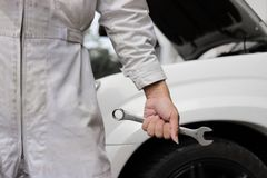 Hands of professional mechanic man in white uniform holding wrench with car in open hood at the repair garage background. Stock Photo