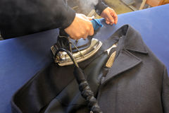 Hands of professional tailor ironing textile with steaming. On the iron board before starting work in traditional tailors shop studio. Real people. Copy space Royalty Free Stock Photo