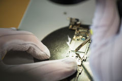 Hands of professional tech repairing small computer components on microscope table using Soldering iron. Closeup Stock Images