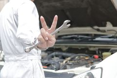 Hands of professional young mechanic man holding wrench and raising two fingers up it is shows fight with job against car in open Royalty Free Stock Images
