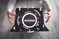Hands protect Dividend text with currency symbols. Business royalty free stock photography