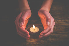 Hands that protect the flame. Of a candle stock image