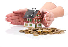Hands protect miniature house with the coins Stock Image