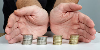 Hands protect money. Hands protect Euro coins money stock photo