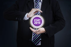 Hands protect start button with numbers 2016. Closeup of businessman hands protecting start button with numbers 2016 Royalty Free Stock Photo