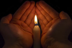 Hands protecting a Candle Stock Image