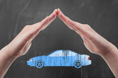Hands protecting car shape as auto insurance concept Stock Photos