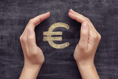 Hands protecting drawn euro sign on black chalkboard background Royalty Free Stock Image