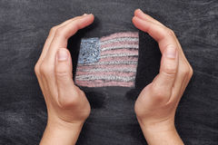 Hands protecting drawn Usa flag on black chalkboard background Royalty Free Stock Photography