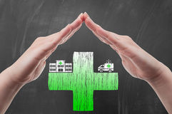 Hands protecting green cross draw on blackboard. As health insurance concept Stock Photo