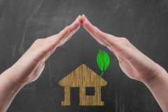 Hands protecting green energy house concept Stock Images