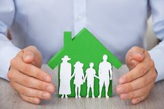 Hands protecting green model house and family Royalty Free Stock Image