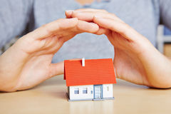 Hands protecting house like insurance stock photos