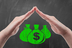 Hands protecting money bags Stock Photos