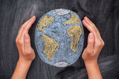 Hands protecting Planet Earth on black chalkboard background Stock Images