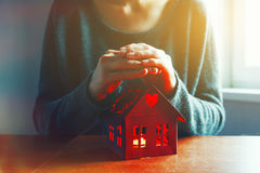 Hands protecting house as symbol of safety Royalty Free Stock Image