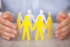 Hands protecting team of paper people Royalty Free Stock Photo