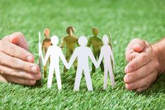 Hands protecting team of paper people Royalty Free Stock Photos