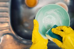 Hands in protective gloves hold a sponge with detergent and wash a plate over the sink in the kitchen