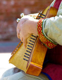 Hands of psaltery player. Hands of old russian psaltery player in folk dress Stock Image