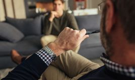 Psychotherapist understanding problems of a male patient. Hands of psychologist holding a pen and listening to men during therapy session. Psychotherapist Royalty Free Stock Photography