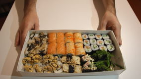 Hands are pulling the box full of assorted sushi close to the camera stock footage