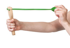 Hands pulling green band of wooden slingshot Royalty Free Stock Photos