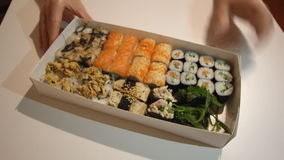 Hands are pulling and moving the box full of assorted sushi close to the camera stock footage