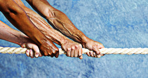 Hands pulling rope. Tug of war with grunge texture royalty free stock photography
