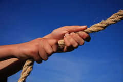Hands Pulling On Rope. Conceptual image - hands pulling on a rope blue sky background. Might signify strength pulling power determination teamwork etc stock images