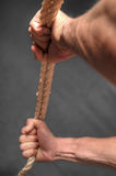 Hands pulling rope over dark background Stock Photos