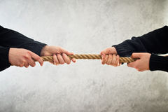 Hands pulling rope to opposite sides. Female hands pulling rope to opposite sides. Rivalry concept royalty free stock photo