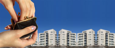 Hands with Purse. Two hands holding small change purse and reaching into it, tall buildings in background Royalty Free Stock Photos
