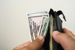 In the hands of a purse in which American dollar bills royalty free stock image