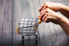 Hands pushing supermarket trolleys filled with pills Royalty Free Stock Photos