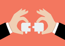 Hands pushing two jigsaw pieces together Stock Images