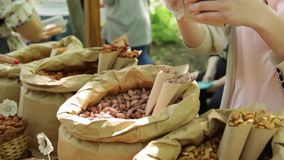 Hands put nuts into bag. Nuts on the counter. stock video footage