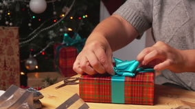 Hands put packed gift under the Christmas tree. Close-up of hands put packed gift under the Christmas tree stock video