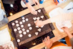 Hands put pink macroons on kitchen scales Stock Image