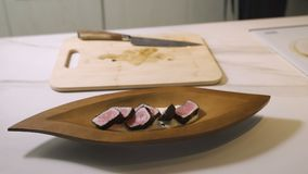 Hands put sushi on plate. Long plate with sushi rolls. Japanese chef gives master class. stock video footage