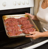 Hands putting beef into ove Stock Images