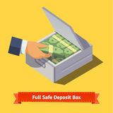 Hands putting cash stack to a safe deposit box Stock Images