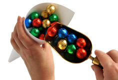 Hands putting colorful candy balls in cone Stock Image
