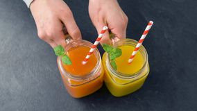 Hands putting fresh juices in mason jars on table