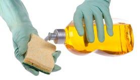 Hands putting liquid dish soap on a sponge Stock Photo