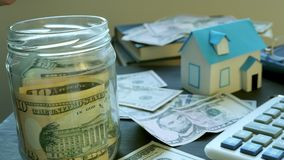 Hands putting money into the jar and model of house. Savings for buying real estate.