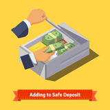 Hands putting money and valuables to a deposit box Stock Image